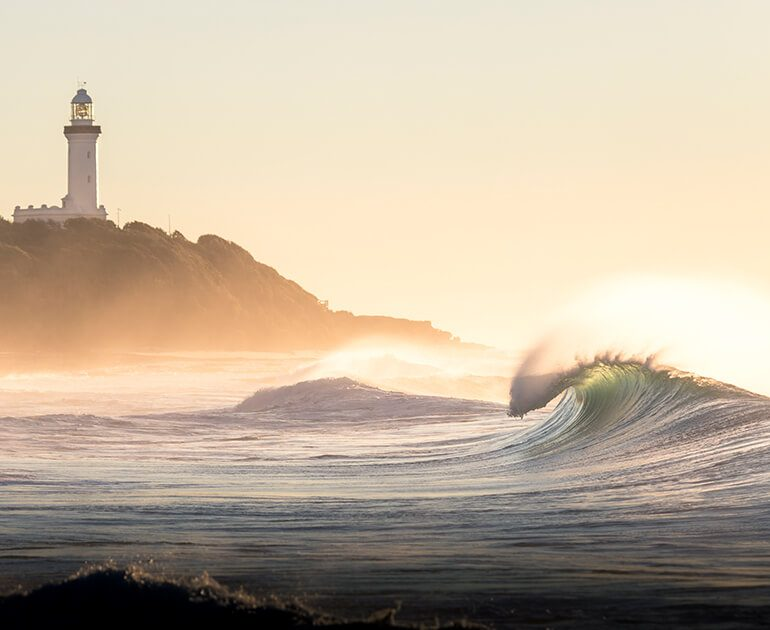 breaking wave with a lighthouse behind