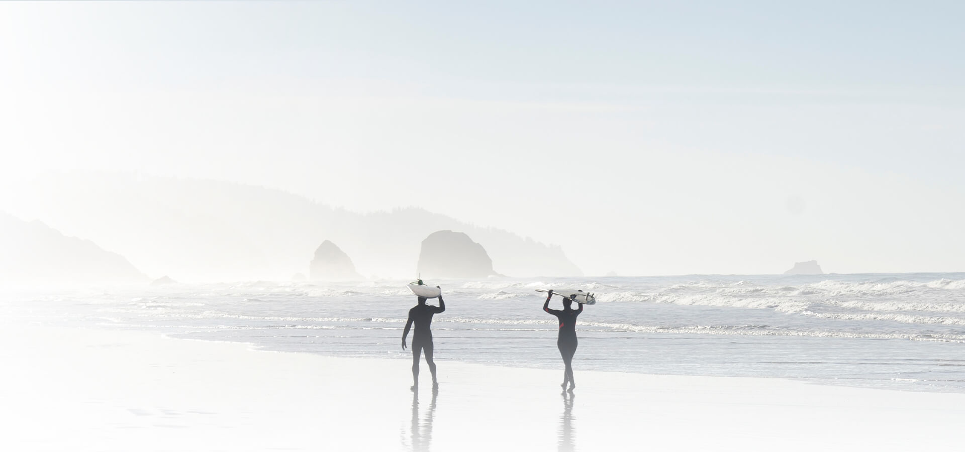 coupe walking on beach with surfboards