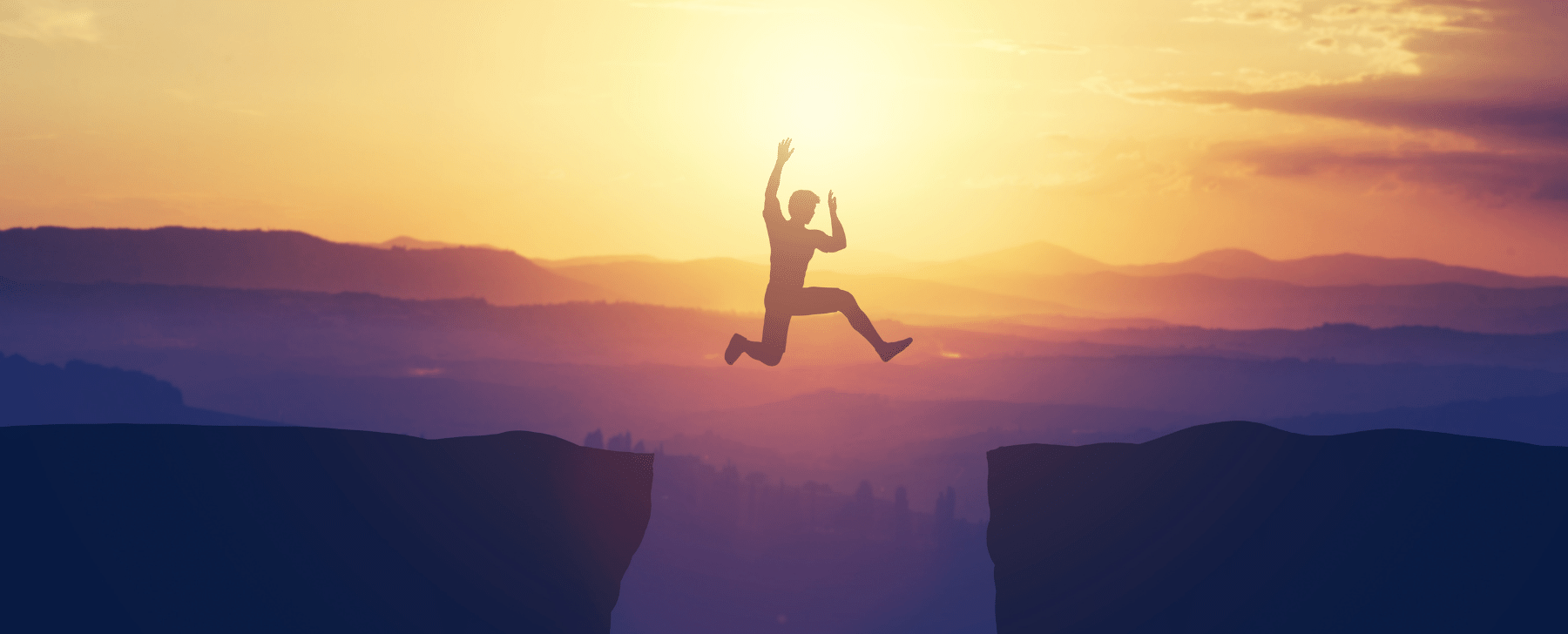 person jumping between two mountains at sunset risk taker