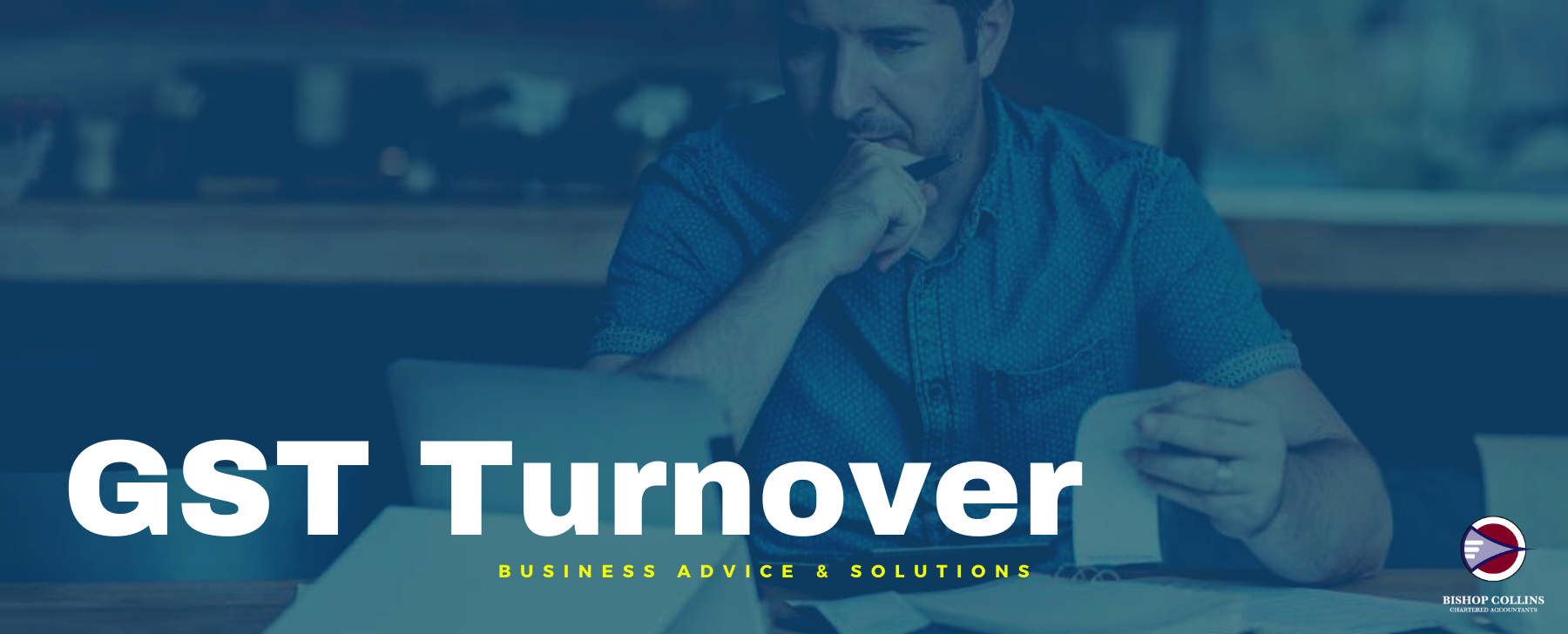 What is GST Turnover business man at a table with computer and figures on paper