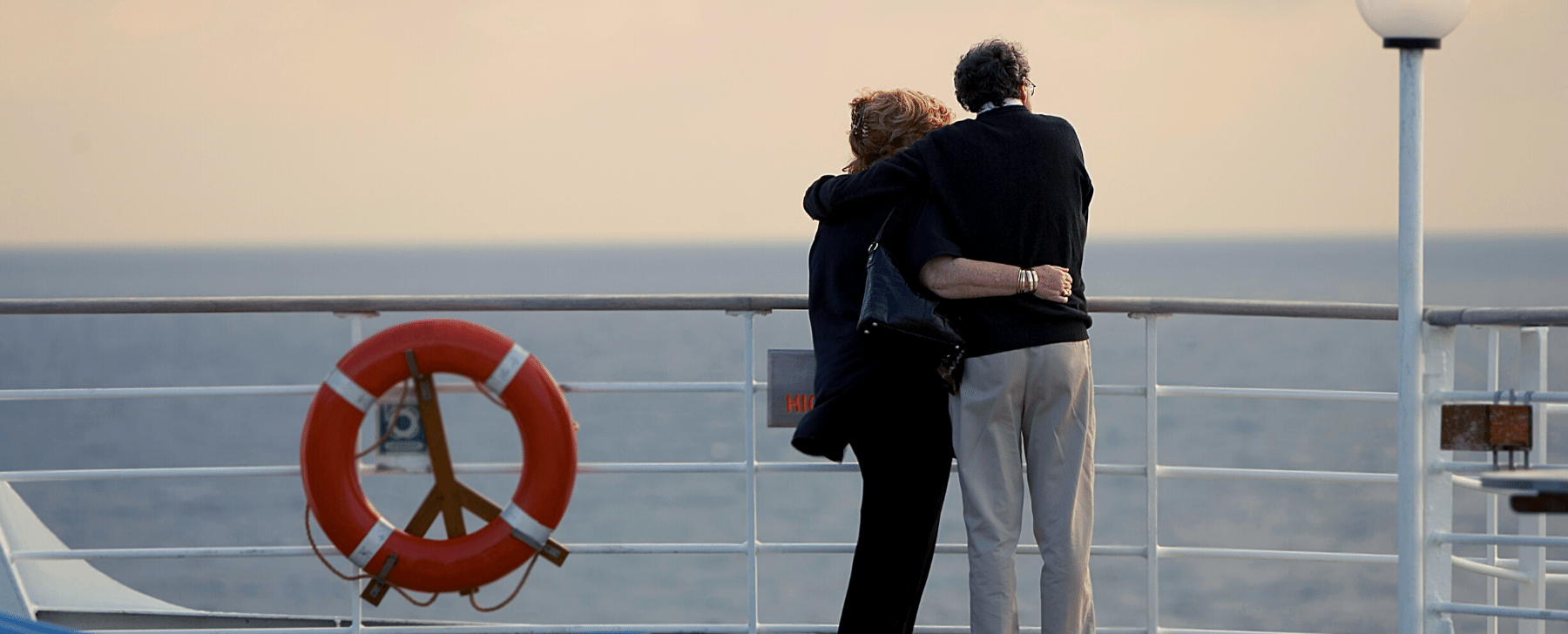 AN ELDERLY COUPLE LOOKING OUT TO SEE HUGGING ON A CRUISE SHIP AT SUNSET RETIREMENT PLANNING