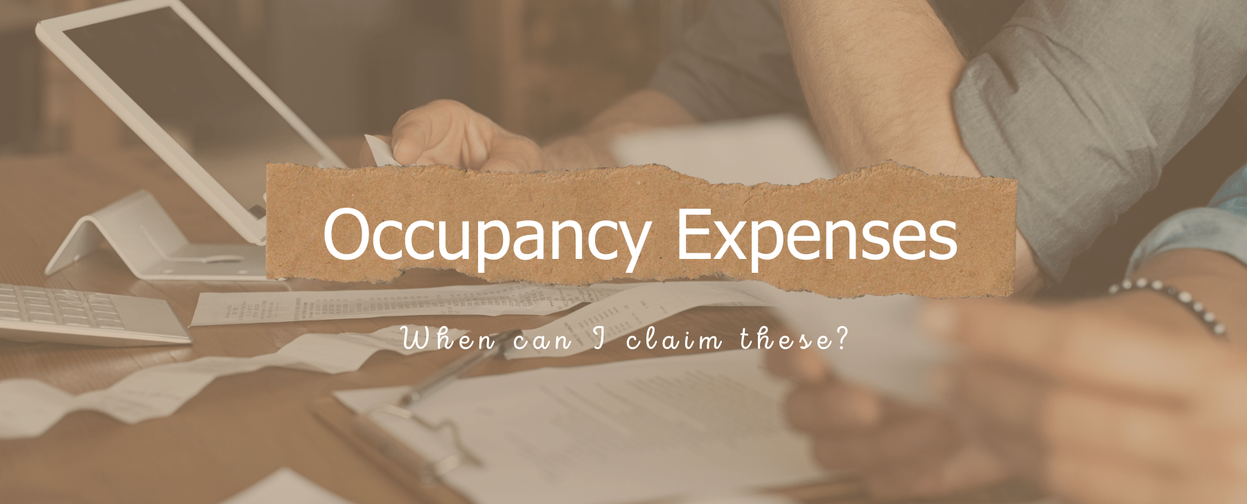 occupancy expenses when can i claim these? background image of expenses on a table with hands sorting through them.