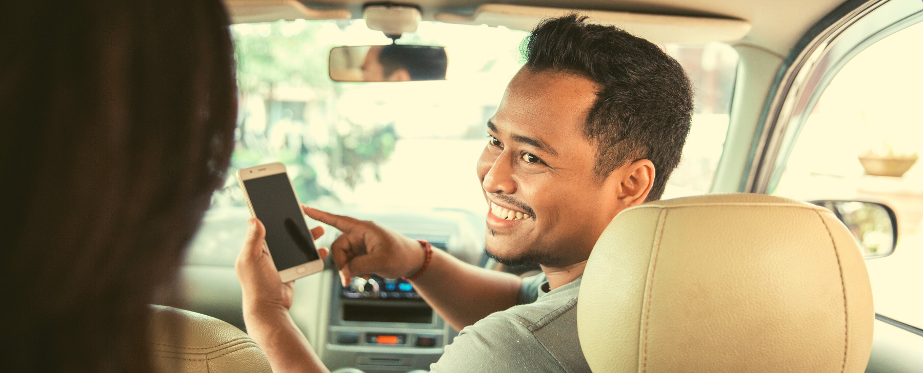 When to register for GST Uber Driver with mobile phone app open looking at passenger in the backseat and smiling,