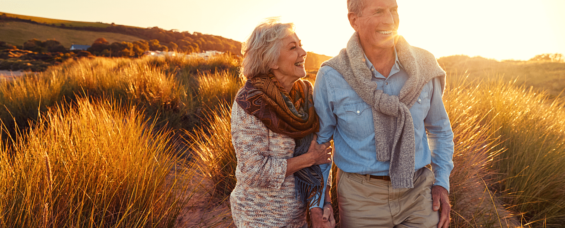 and older couple standing in front of a grassy field at sunset with golden colours retirement planning