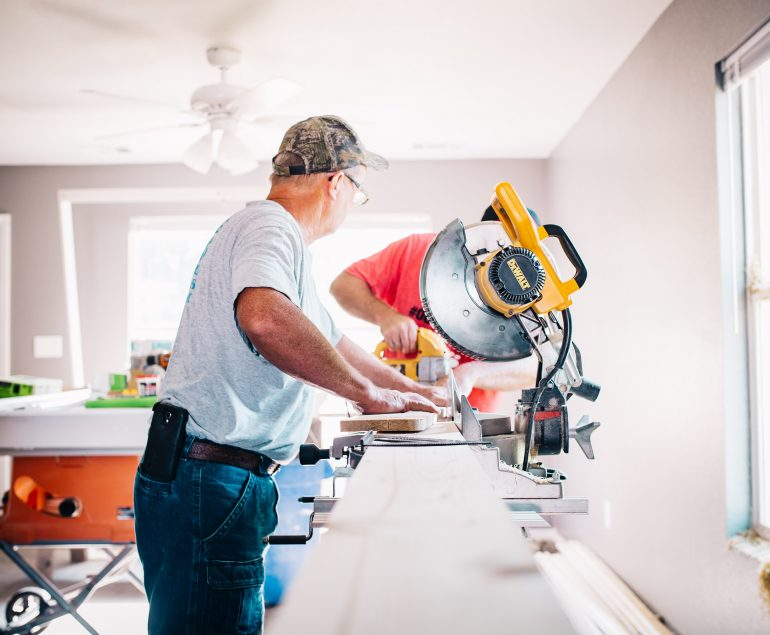 small business owner camera looking down a long piece of wood that is being cut by a circular saw and a man in jeans and a white shirt standing at the point where the saw is holding the wood down cutting inside a lounge room type area. Instant asset tax write off