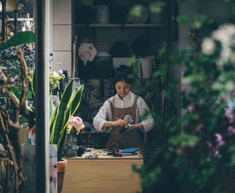 small business start up. lady in the background sorting flowers for a florist. flowers in the foreground out of focus. small business