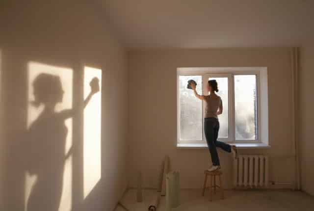 Woman standing up a wood chair cleaning a window.